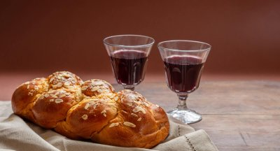 Challah bread with two glasses of red wine on wooden table